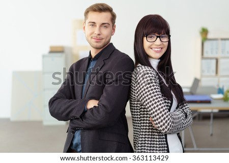 Confident successful management team standing back to back in the office smiling at the camera with folded arms, man and woman - stock photo