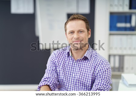 Confident successful smiling businessman sitting at his desk in the office looking at the camera with a friendly smile