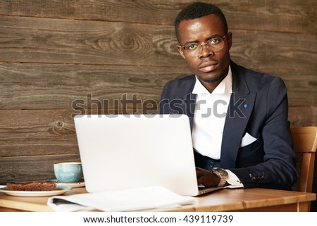 Confident successful young dark-skinned entrepreneur in formal wear working on laptop, looking at the camera with full of thoughts face expression, sitting at the table, having coffee at a cafe - stock photo