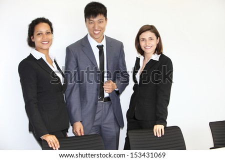 Confident successful young multiethnic business team standing together in the office smiling at the camera - stock photo