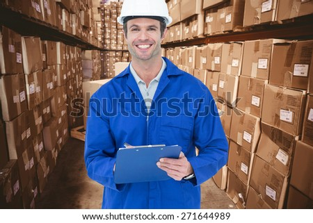 Confident supervisor writing notes against boxes in warehouse - stock photo