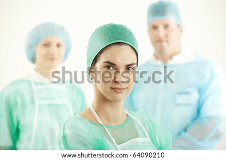 Confident surgeon with colleagues in background, wearing hospital scrubs.?