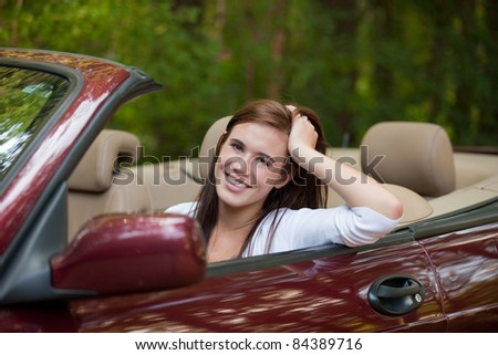Confident Teenager Female Driver Arm Out in Convertible - stock photo