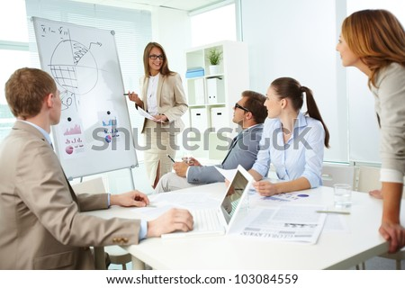 Confident top manager standing by the whiteboard and explaining her strategy at meeting - stock photo