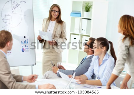 Confident top manager standing by the whiteboard and making report at meeting - stock photo