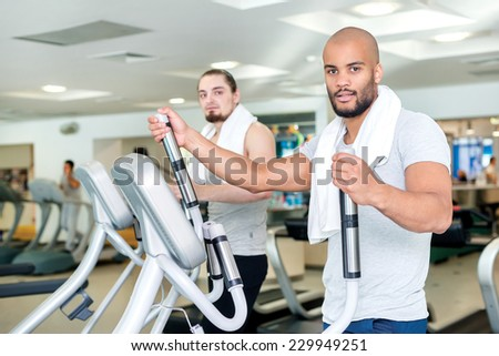 Confident training of two friends in the gym in the cardio room. Two athletes engaged in the simulator gym - stock photo