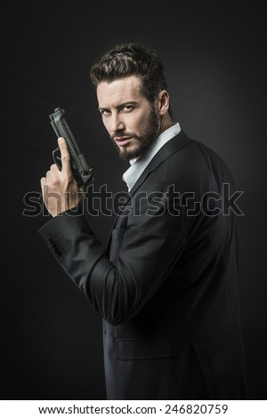 Confident undercover agent with a gun against dark background - stock photo