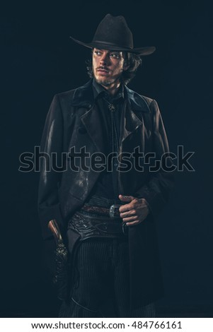 Confident vintage 1900 cowboy showing revolver. Ready to shoot. Studio shot.