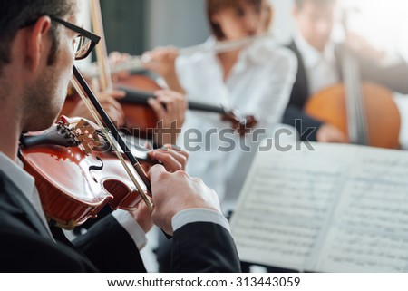 Confident violinist playing his instrument and reading a music sheet, classical music symphony orchestra performing on background - stock photo