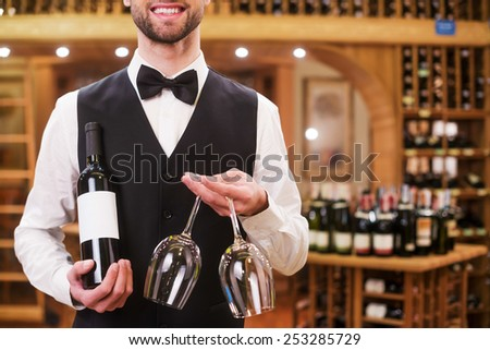 Confident waiter. Handsome young man in waistcoat and bow tie holding bottle and glasses while standing in liquor store  - stock photo