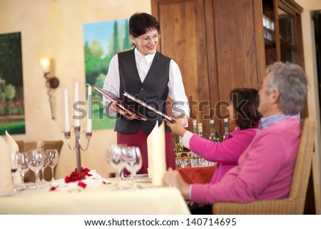 confident waitress passing the menu to couple sitting at the table - stock photo