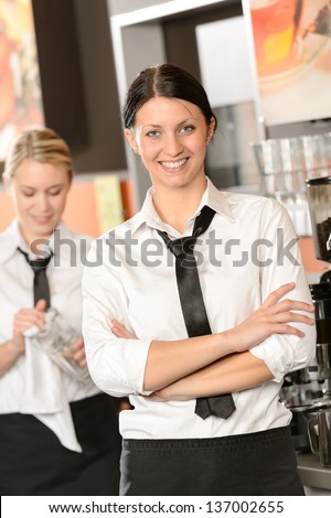 Confident waitress posing in cafe in uniform