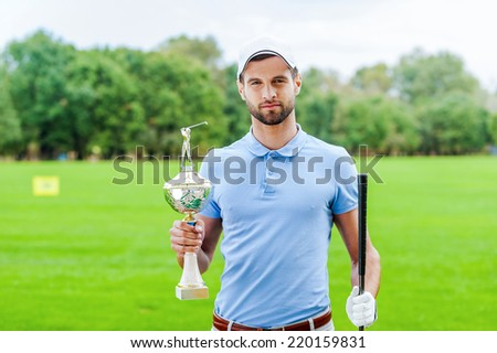 Confident winner. Confident golfer holding golf ball and driver while standing on golf course and looking over shoulder - stock photo