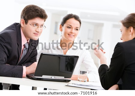 Confident woman explains terms of the treaty to business people - stock photo
