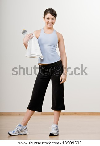 Confident woman in sportswear holding towel and water bottle - stock photo