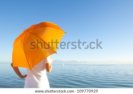 Confident woman in white shirt and pants standing with orange umbrella at peaceful ocean at Shark Bay, Western Australia, isolated with sea and blue sunset sky as background and copy space. - stock photo