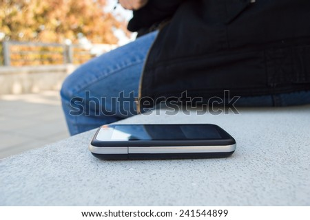 confident woman leaves the phone on the park bench - stock photo