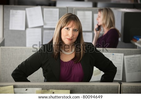 Confident woman office worker stands in her cubicle - stock photo