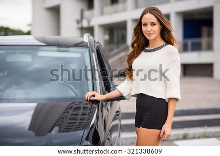 Confident woman portrait close to her car in the city. Filtered image.