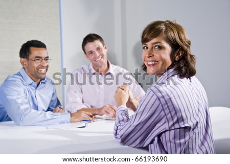 Confident woman (40s) in business meeting, businessmen across table