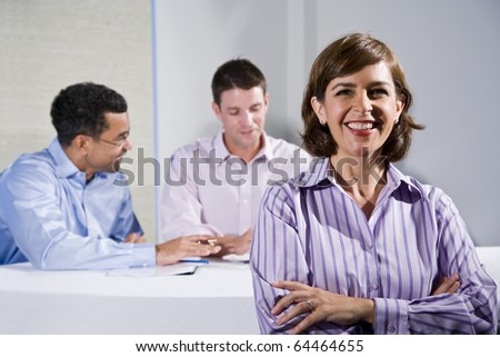 Confident woman (40s) in business meeting, businessmen talking in background - stock photo