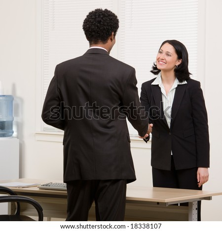 Confident woman shaking hands with co-worker at desk in agreement - stock photo