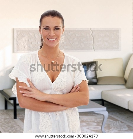 Confident woman smiling at home, arms crossed, looking at camera. - stock photo