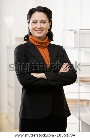 Confident woman standing with arms crossed - stock photo
