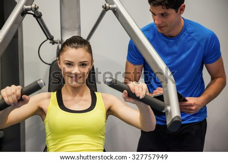 Confident woman using weights machine with trainer at the gym - stock photo