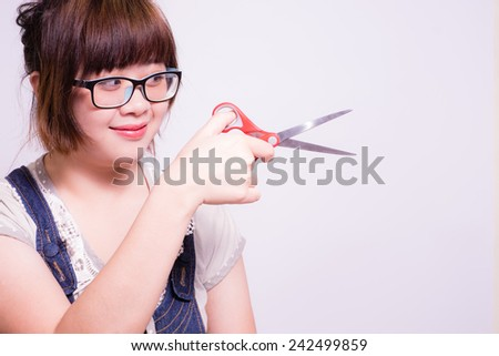 confident woman with her scissors, she's cutting something. - stock photo