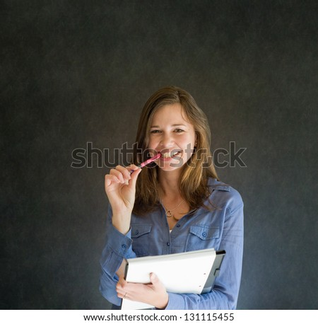 Confident woman with notepad and pen against a dark blackboard background
