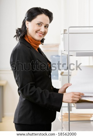 Confident woman working in office - stock photo