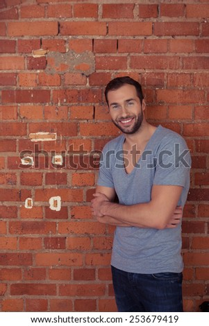 Confident young bearded man standing with folded arms leaning on a red brick wall smiling at the camera, with copyspace - stock photo