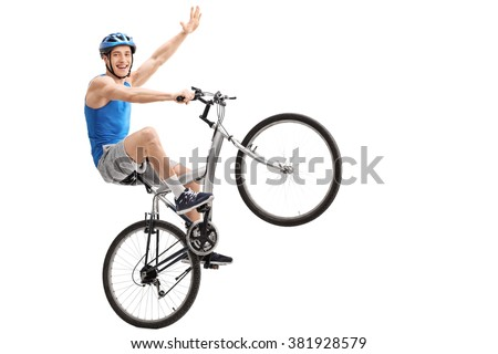 Confident young biker performing a wheelie and holding the bike with one hand isolated on white background