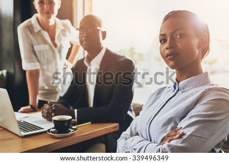 Confident young black business woman sitting in front of other business people - stock photo