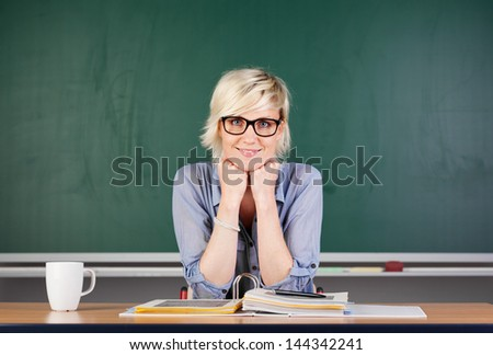 Confident young blond female teacher against chalkboard - stock photo