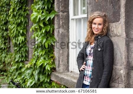 Confident young blond woman smiling an leaning against stone wall - stock photo