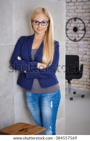 Confident young blonde woman standing against wall arms crossed, smiling happy, looking at camera. - stock photo