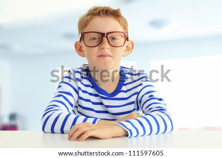 Confident young boy in a striped shirt sitting in the classroom and smiles at the camera. Horizontal shot. - stock photo