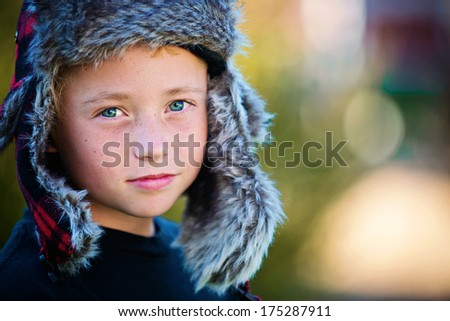Confident young boy in winter hat - stock photo