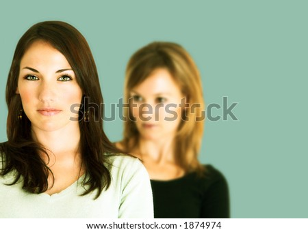 Confident young brunette with arms crossed and her jealous opponent in the background - stock photo