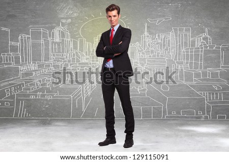 confident young business man standing in front of a sketch of a big city - stock photo