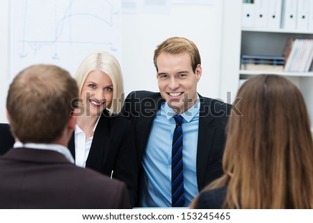 Confident young business team with a smiling handsome man and woman sitting side by side in a meeting facing the camera, view between a man and a woman with their backs to the camera - stock photo