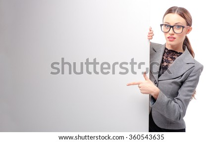 Confident young business woman wearing glasses showing blank signboard pointing with her finger, isolated on white background - stock photo