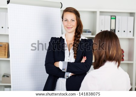 Confident young business woman with a blank white flip chart with copyspace standing smiling at the camera with folded arms - stock photo