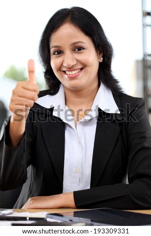 Confident young business woman with thumbs up gesture - stock photo