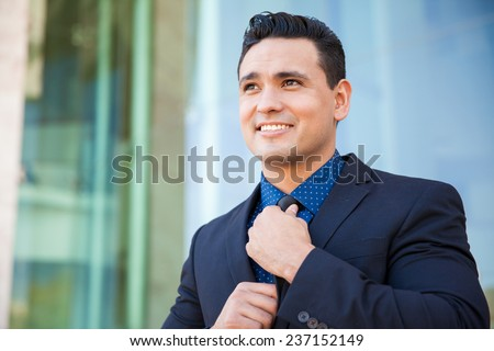 Confident young businessman fixing his tie and getting ready for a business presentation - stock photo