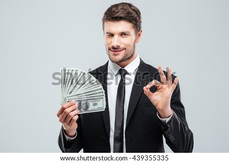 Confident young businessman holding money and showing ok sign over white background - stock photo