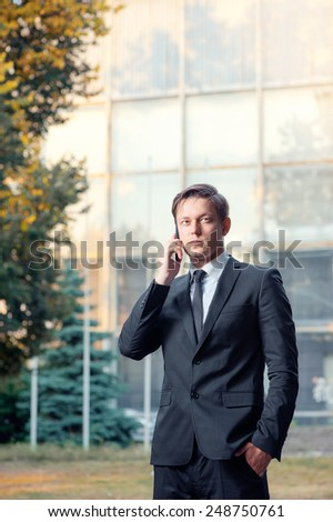 Confident young businessman in suit and tie talking on the mobile phone looking away while standing outdoors with office building in the background