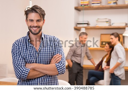 Confident young businessman keeping arms crossed and standing while colleagues on background. Smiling designer with group of colleagues meeting in office. Happy successful man looking at camera. - stock photo